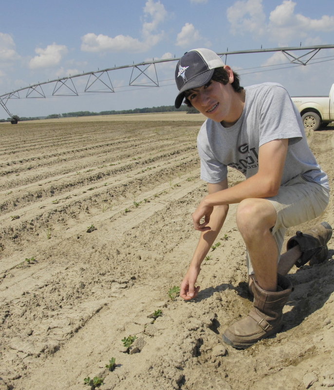 Payson Trawick took a break from planting cotton to check on the irrigation in the peanut field of theirs.